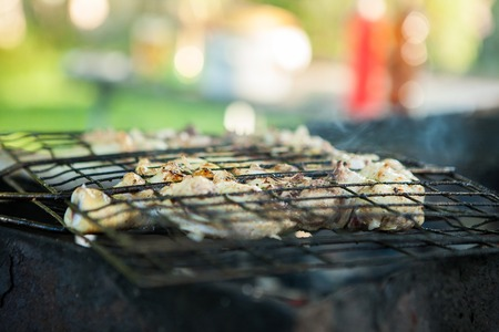 roasted duck on the charcoal grill. Preparation of meat slices in sauce on fire. Stock Photo