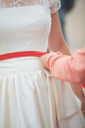 tightening: Female hands tightening a corset to the bride Stock Photo