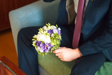 well-dressed man holding a bouquet of flowers, white roses. Holidays and celebrations. Wedding day