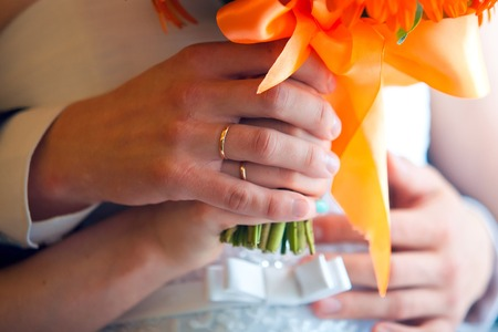 arm bouquet: Man and womans hands with wedding rings and wedding bouquet of flowers. Bride and groom holding hands with wedding rings