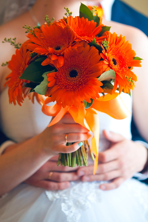 Bride and groom holding bridal bouquet close up. Stock Photo