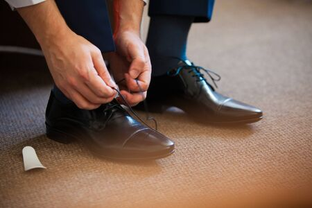 shoe strings: Man ties his shiney new black leather business shoes