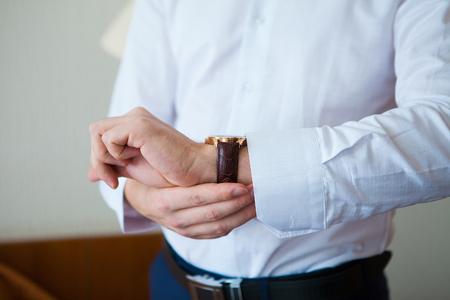 rushing hour: Elegant businessman correcting his clocks and cufflinks.