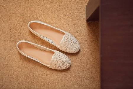 wooden shoes: Pair of new unlaced womans shoes on a white wooden floor.