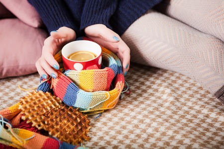 legwarmers: Soft cozy photo of slim tan woman in warm sweater on the bed with cup of tea in hands, top view point. Girl sitting on checkered plaid near and cookies