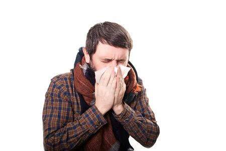 snotty: young sick and ill man in bed holding tissue cleaning snotty nose having temperature feeling bad infected by winter grippe virus in flu and influenza health care concept.