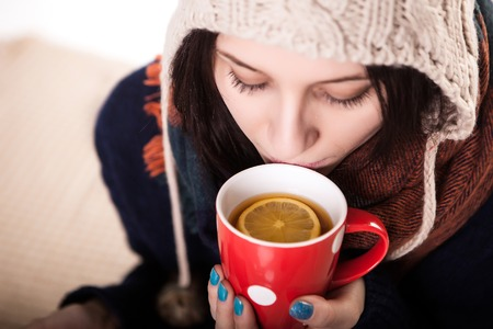 appreciating: Woman enjoying a large cup of freshly brewed hot tea as she relaxes on a sofa in the living room. Stock Photo
