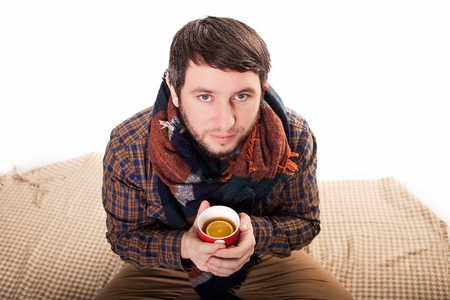 Portrait of a sick man with a fever wrapped in a blanket and holding a warm tea cup