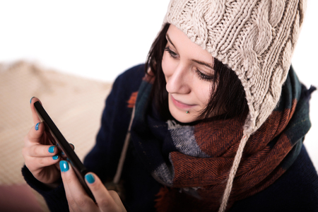 Typing a message for you. Beautiful young black hair women holding mobile phone and looking at it while standing against white background