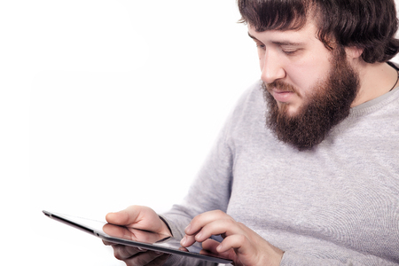 Bearded blogger typing text information for publishing new story on internet websites via modern touch pad connecting to wireless 4G.Attractive man searching information on digital tablet device, close-up