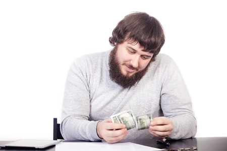 Money doesnt bring buy happiness. Close Up portrait young man holding money cash, human looks at cash, sitting at the table, isolate white background Stock Photo