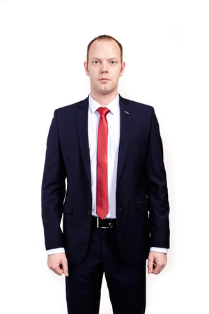 Respectable senior businessman, wearing black suit, white shirt and red tie standing on white background Standard-Bild