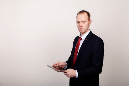 welldressed: elegant young businessman keeps the tablet in hands, watching straight Stock Photo