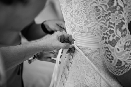 bodice: Bridesmaids help put on tie corset on wedding dress closeup b lack and white