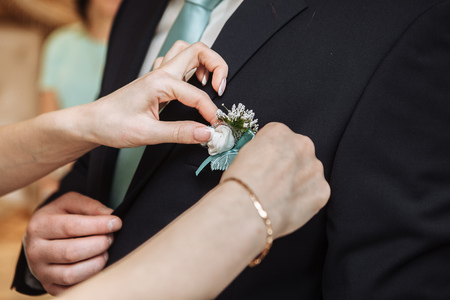 pinning: Woman pinning the boutonniere on the grooms jacket. Close up picture. Unrecognizable man. Horizontal format
