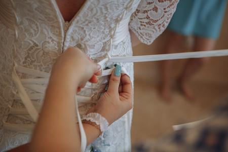 Closeup toned photo of beautiful bride tying up her wedding dress Stock Photo
