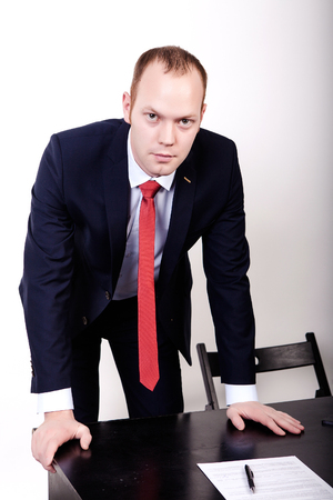 Serious looking designer man leaning on a table