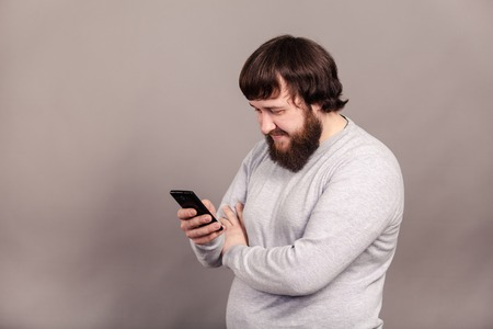 A man with a beard reads news in his smartphone, on grey background Imagens