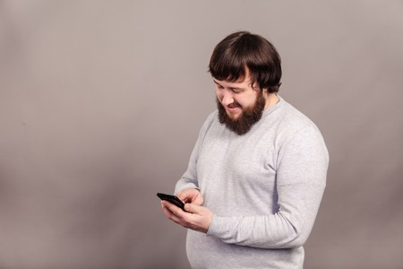 Handsome young businessman with mustache using smartphone isolated over gray background