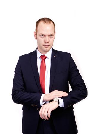 Time is money, man in formal wear pointing at his watch and looking into the camera while standing against white background
