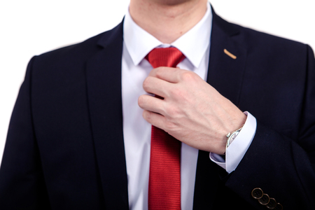 Young Business Man Fixing his red Tie, wedding tie, close-up in front of white background