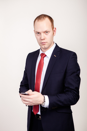 Groom Used Smartphone. The man in a white shirt and black suit with a red tie, hold mobile phone, looking straight, behind man white background Imagens