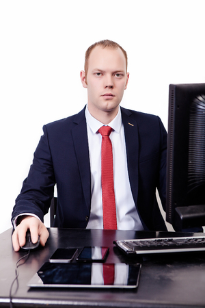 A businessman looks straight, right-handed uses a computer mouse, a tablet on a desk, a computer in front of a man, on the white background