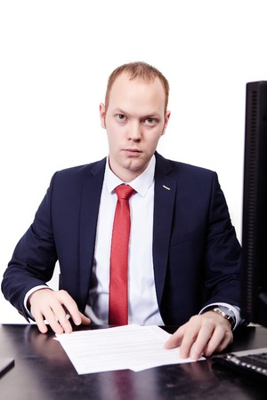 At an interview, general manager in suit with red tie with documents, looks straight. in front of white background