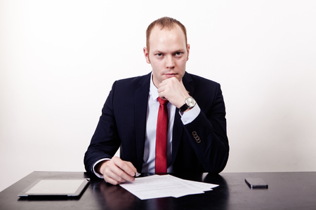 Thoughtful businessman in formal wear holding hand on chin while sitting at his working place, documents, phone, the tablet on table, on the white background