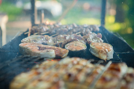 Three pieces of rich roasted salmon fish meat mix, on the grill, on a warm summer July day Imagens