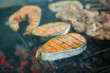 Grilled salmon steaks on a grill. Fire flame grill. Restaurant and garden kitchen. Garden party.Healthy dish