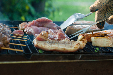Man grilling an assortment of meat and kebabs on a portable barbecue lifting a t-bone steak with a pair of tongs in a close up view of his hand Imagens