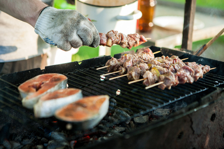 Hand of a young man, cooking a mix of fresh steak from fish and grilled meat on a summer warm day Imagens