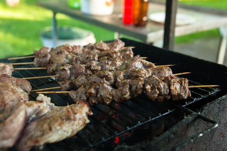 Marinated shashlik preparing on a barbecue grill over charcoal. Shashlik or Shish kebab popular in Eastern Europe.