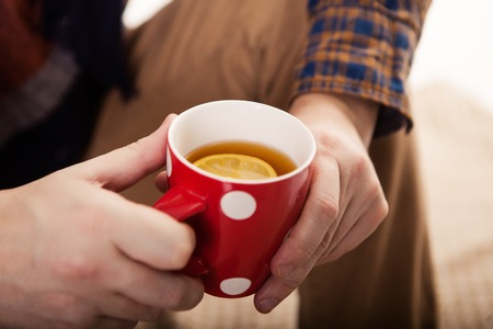 Close-up of male hands holding red mug Imagens