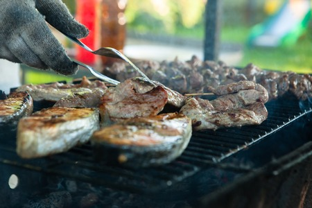 Man cooking marinated shashlik or shish kebab, chicken meat and fish grilling on metal skewer, close up.