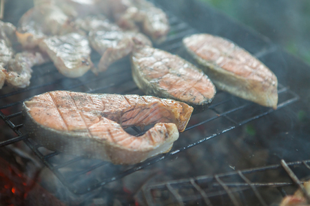 Three pieces of grilled salmon fish steak barbecue meal cooking, cooked on a barbecue grill, close-up