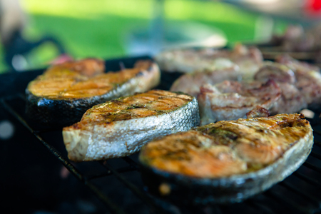 Cooking fresh fish fried BBQ with a delicious crispy golden crust in a grill over an open fire in a village Stock Photo