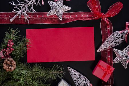 envelope decoration: Winter frame: christmas decoration surrounding red envelope on black background Stock Photo