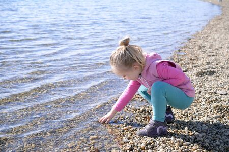 girl squatting: Little girl is playig at the lake Stock Photo