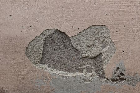 A wall with plaster fallen off leaving a hole that has the shape of an elephant