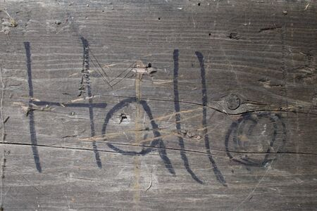 Old weathered wooden tile with hallo written in black on it