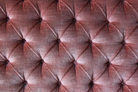 Red diamond pattern with buttons, old vintage sofa, shiny red velvet 写真素材