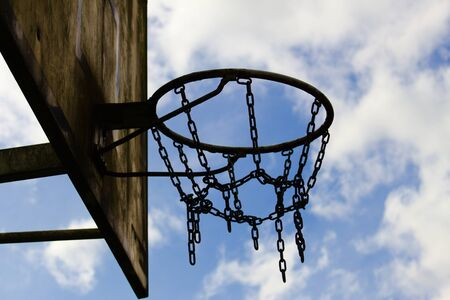 Old basketball chain basket close up view before cloudy sky Standard-Bild - 133415721