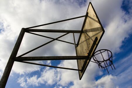 Old basketball chain basket slanted view before cloudy sky Standard-Bild - 133415725