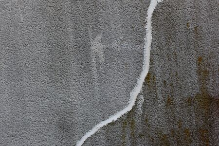 Concrete wall with crack running down repaired with white concrete patching putty