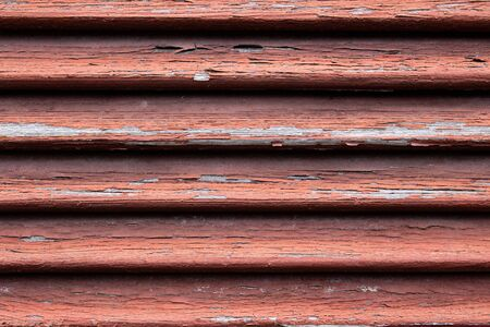 Close up of a dirty old red wooden window shutter with weathered and cracked paint peeling off