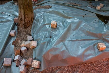 Cobblestones weigh down a plastic sheet that is covering a paving construction site