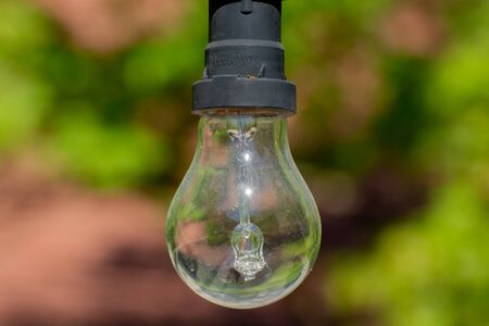 Close up of a dirty old light bulb hanging on a light chain in a park, bokeh