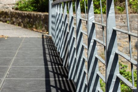Slanted view of a metal railing on a bridge casting shadows with natural stone walls in the background, focus on foreground